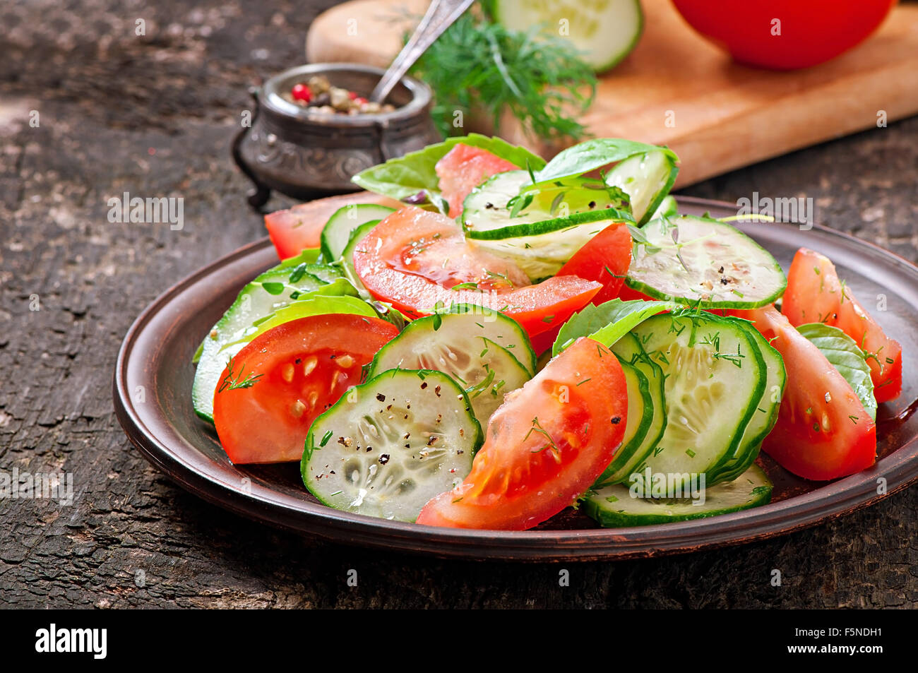 Tomato and cucumber salad with black pepper and basil - Stock Image