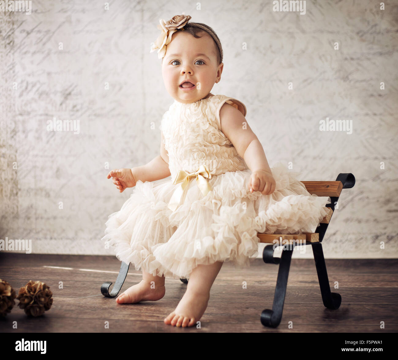 Elegant little girl sitting on the tiny bench - Stock Image