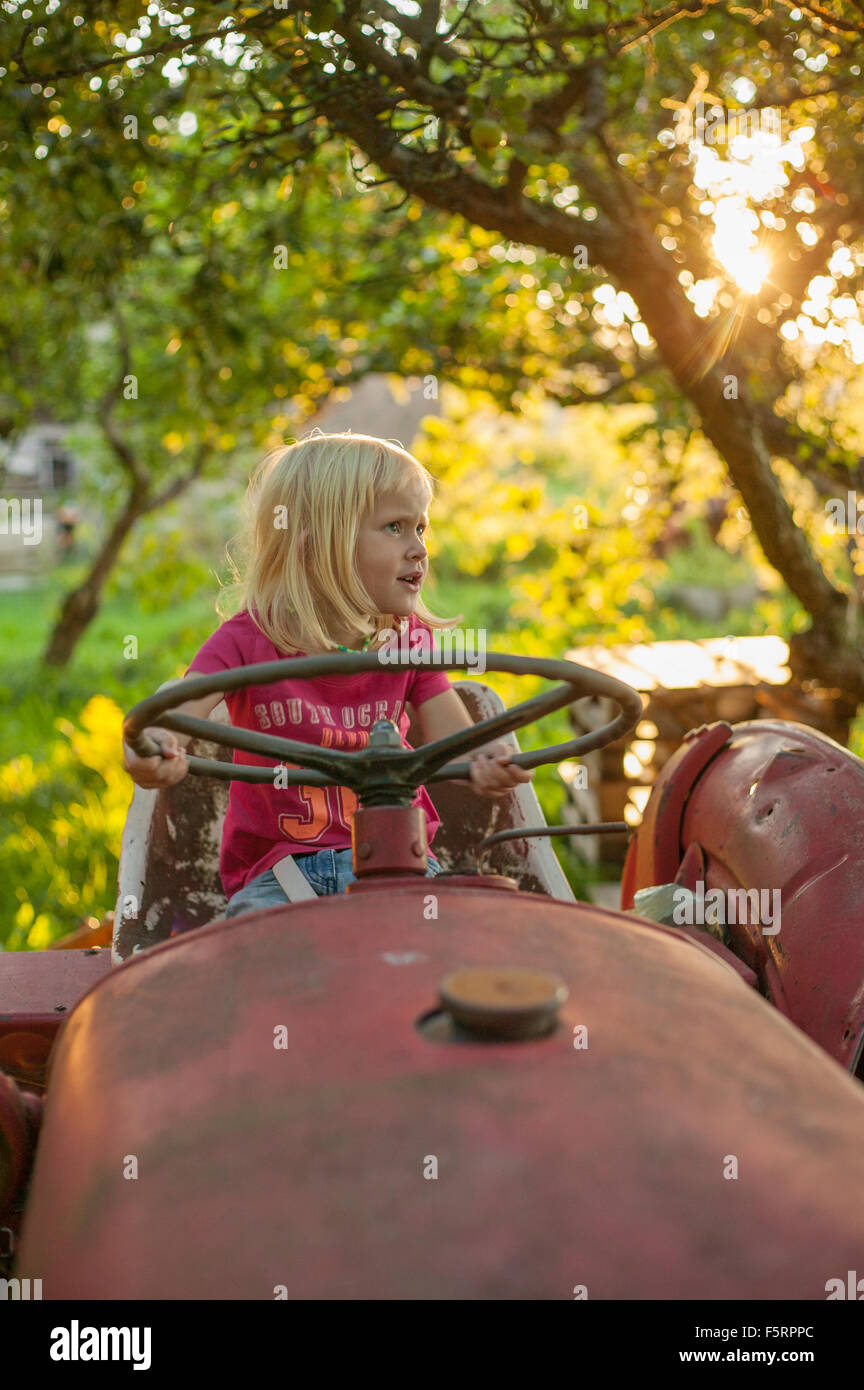 Sweden, Skane, Osterlen, Girl (4-5) on tractor - Stock Image