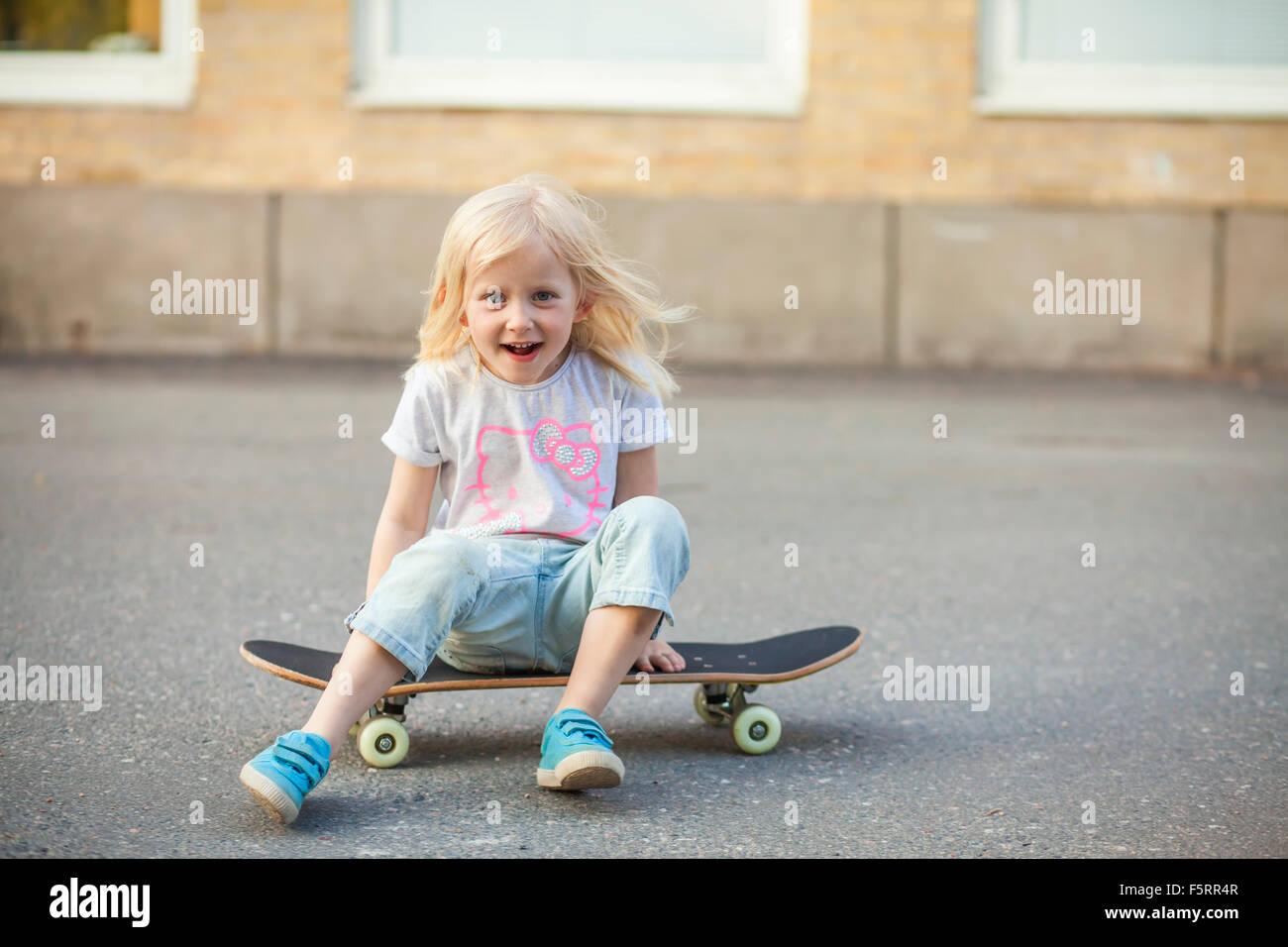 Sweden, Vastergotland, Lerum, Girl (6-7) sitting on skateboard - Stock Image