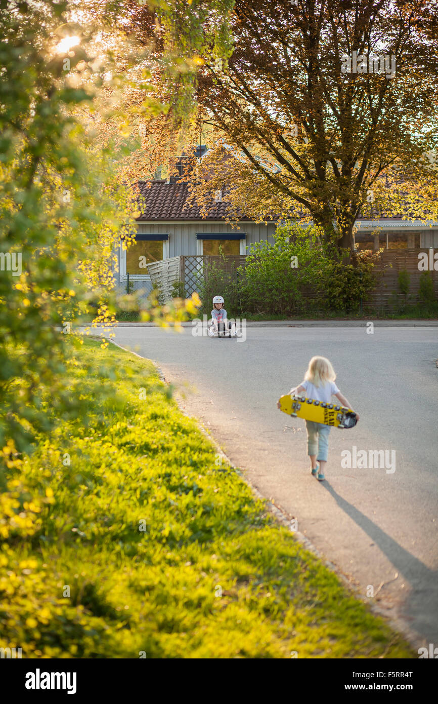 Sweden, Vastergotland, Lerum, Girl (6-7) walking to boy (8-9) with skateboard - Stock Image