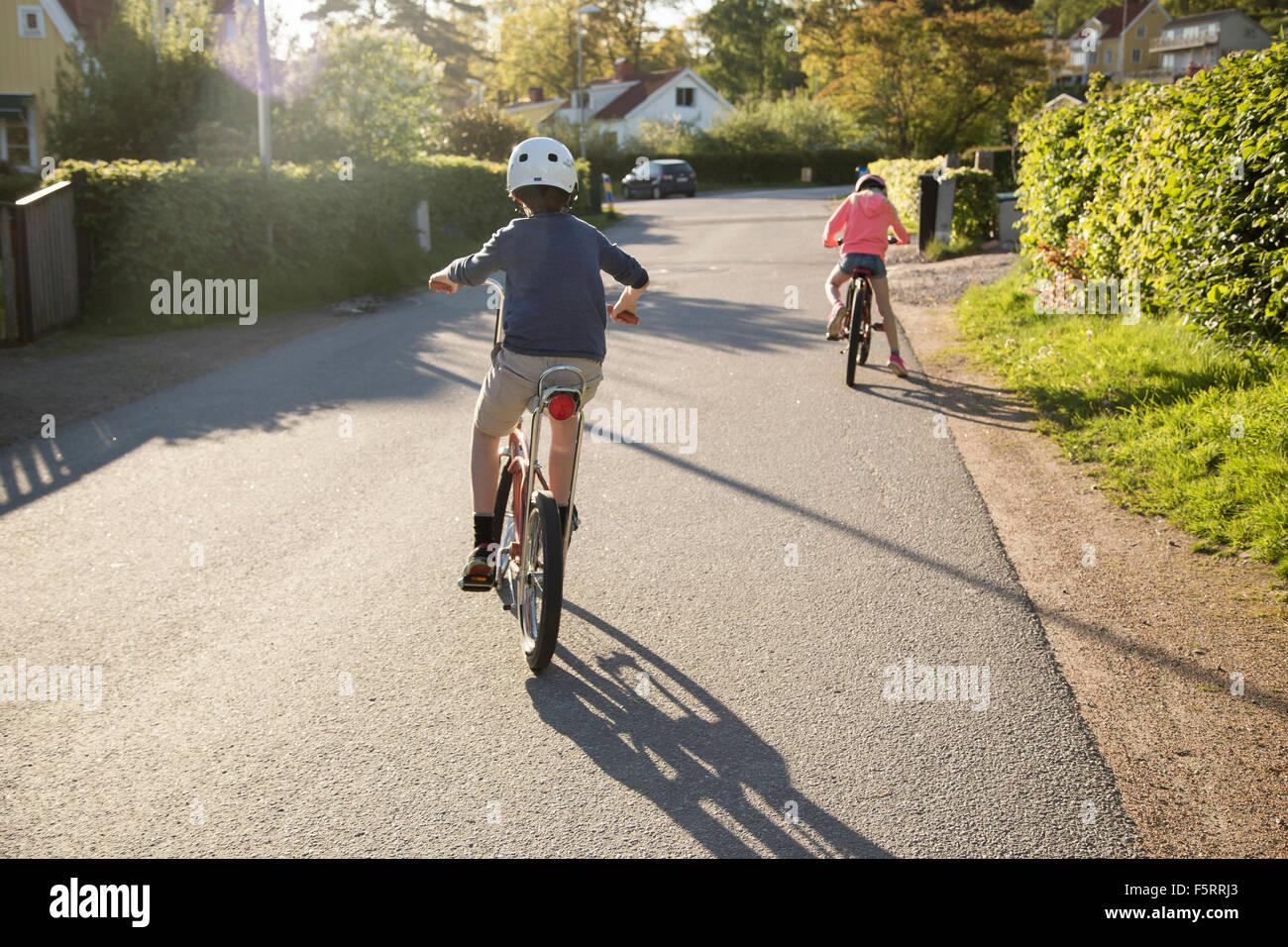 Sweden, Vastergotland, Lerum, Children (10-11, 12-13) cycling in sunny day - Stock Image