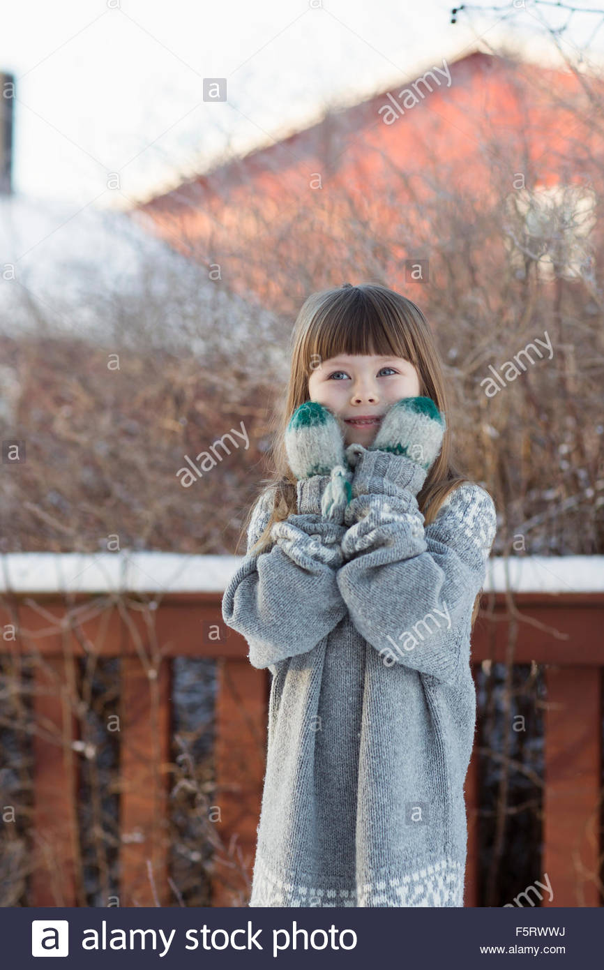 Sweden, Vasterbotten, Little girl (4-5) wearing sweater and mittens - Stock Image