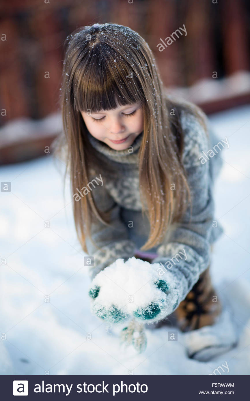Sweden, Vasterbotten, Little girl (4-5) playing with snow - Stock Image