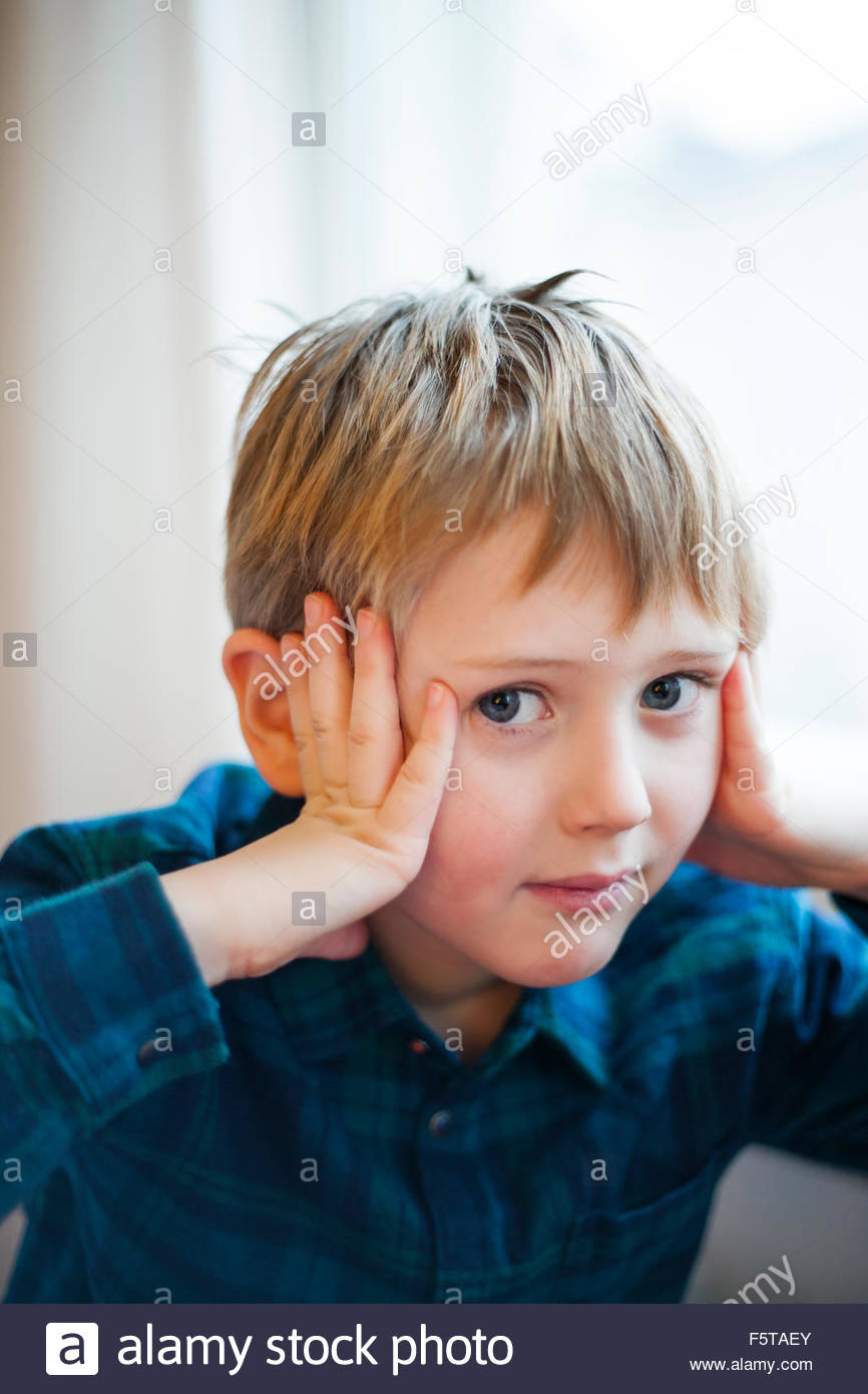 Finland, Boy (6-7) holding head in hands - Stock Image