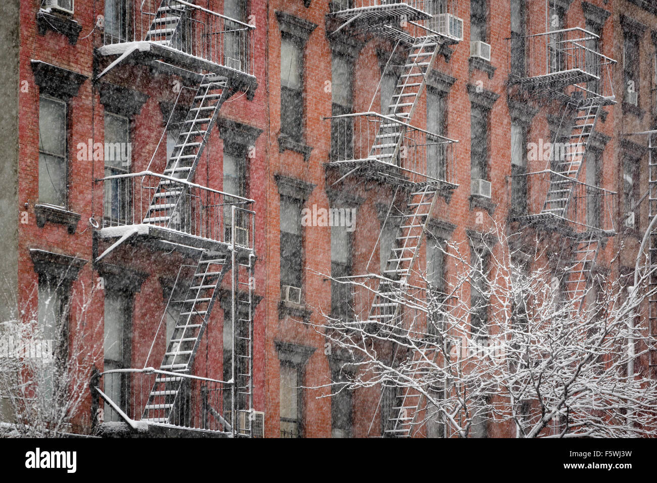 Facade of Chelsea brick building with fire escapes covered in snow during a winter snowfall, Manhattan, New York - Stock Image
