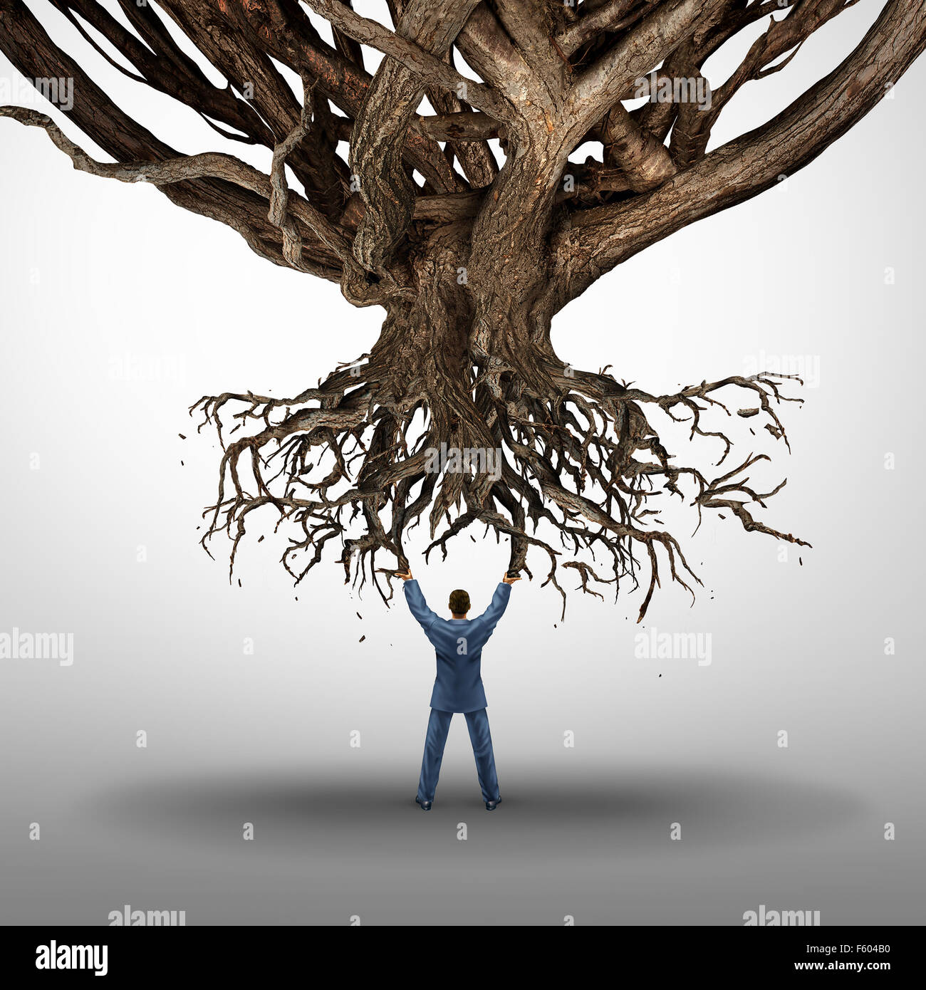 Uprooting and power concept and growt mamnagement symbol as a businessman holding up an uprooted tree as an icon - Stock Image
