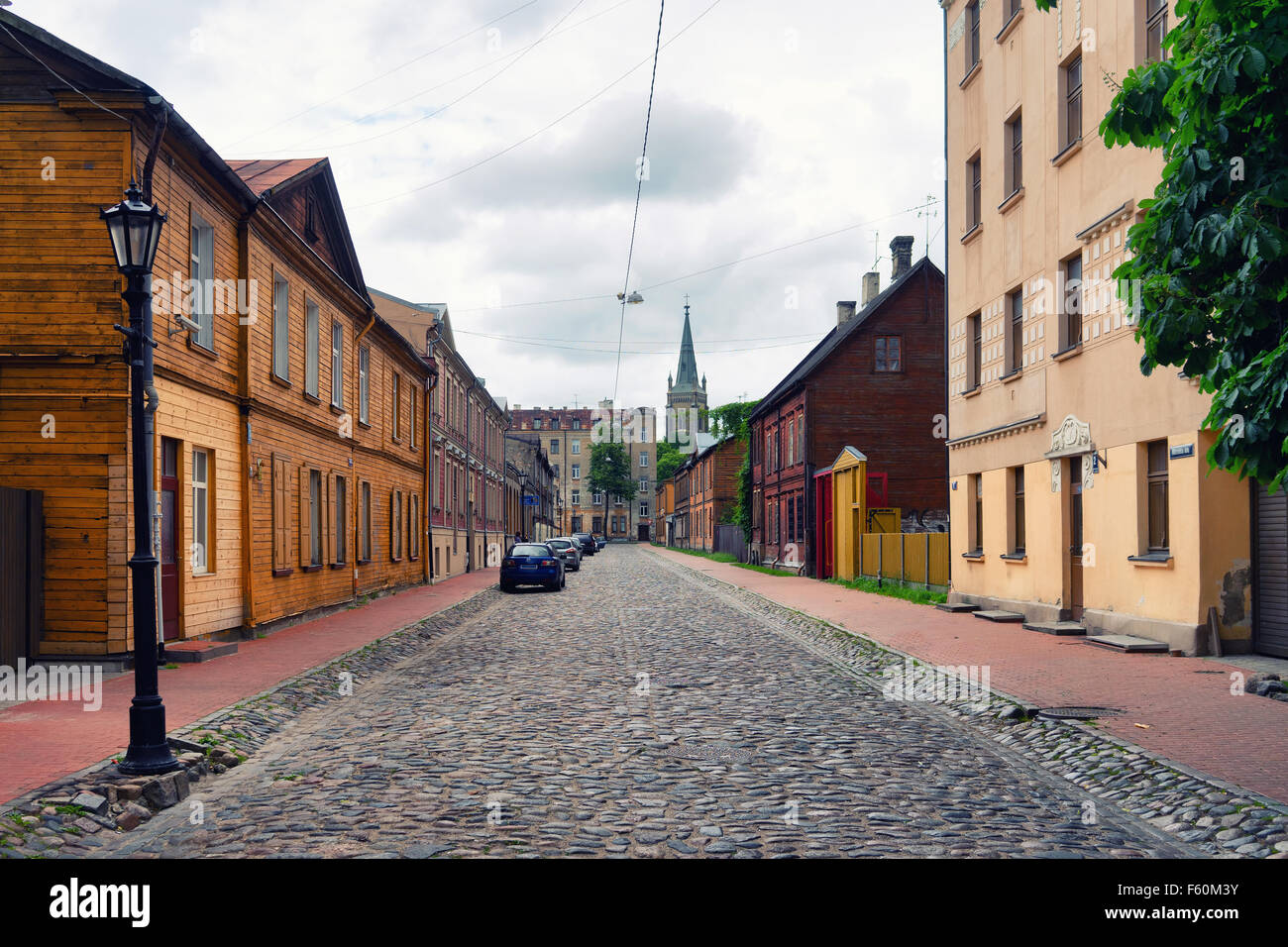Old street with red sidewalks and paving stones on the road in the old city of Riga in spring. Murnieku iela, Riga, - Stock Image