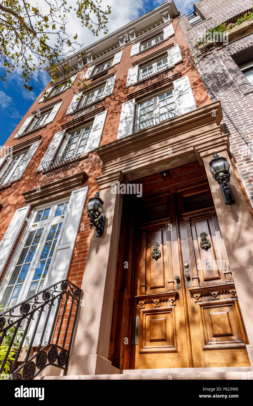 Four-storey townhouse in Chelsea, Manhattan. Typical New York City townhouse architecture with wooden door and brick - Stock Image