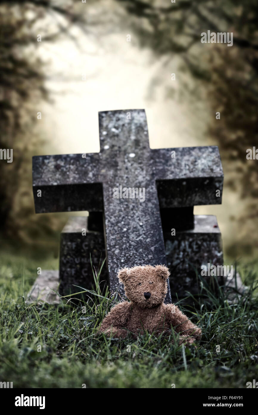 a grave with a teddy bear - Stock Image