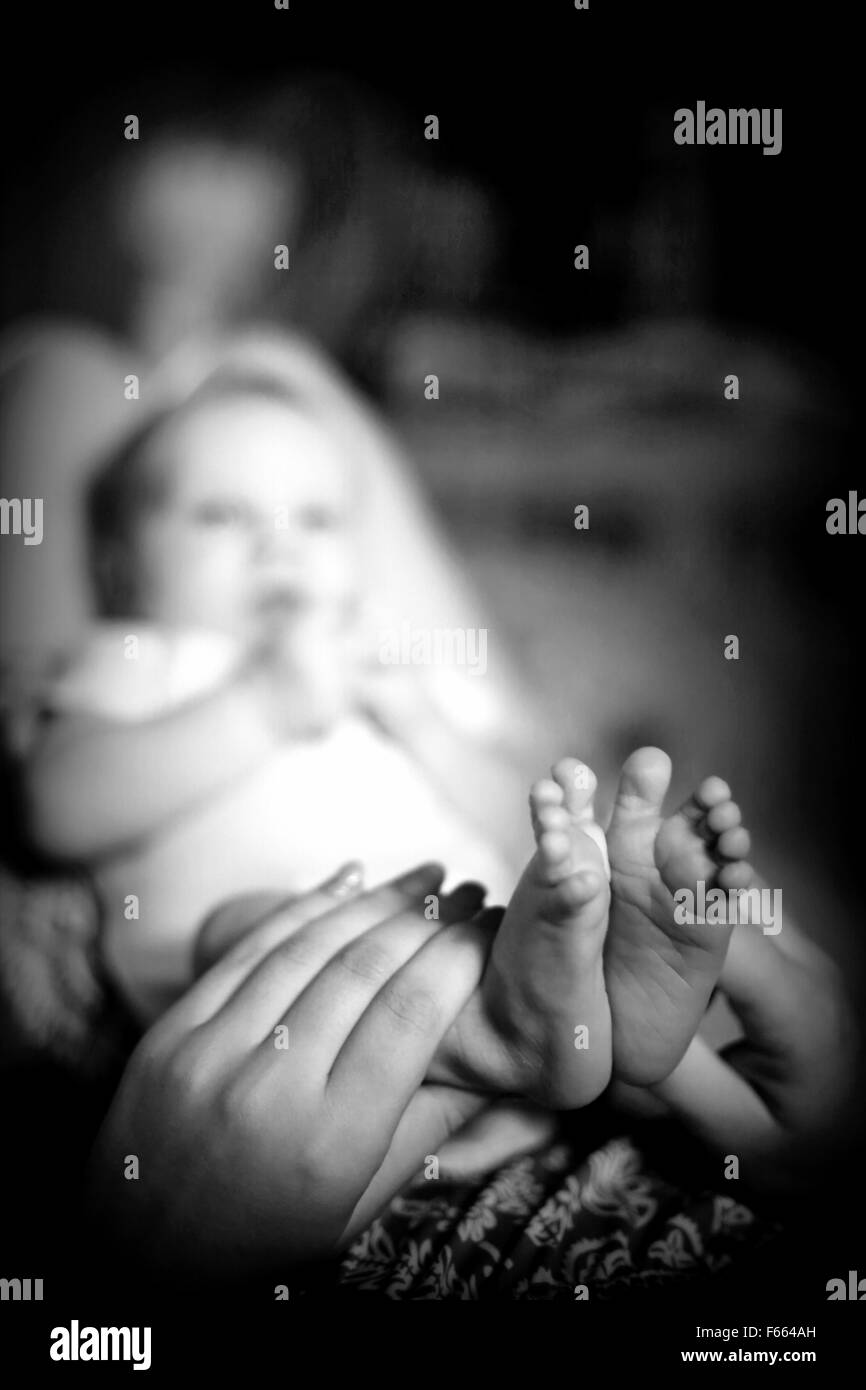 Mother holding legs of her small newborn child and looking at the cute  tiny toes - Stock Image