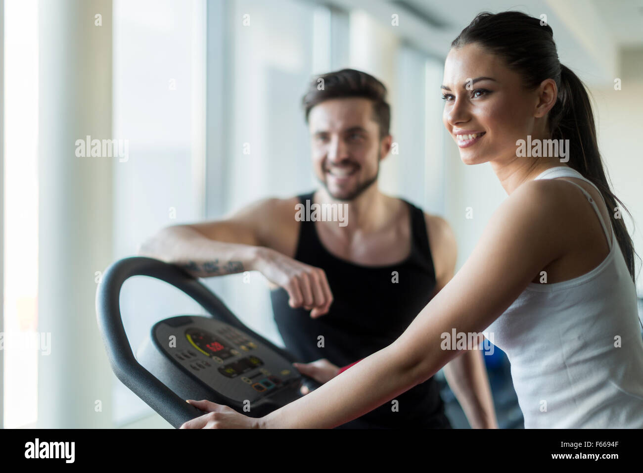 Beautiful, young people talking in a gym while working out and burning calories - Stock Image