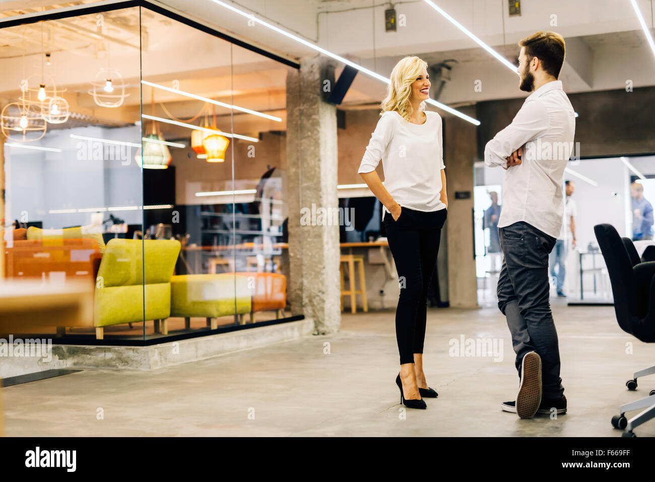 Two intelligent coworkers talking in a modern office - Stock Image
