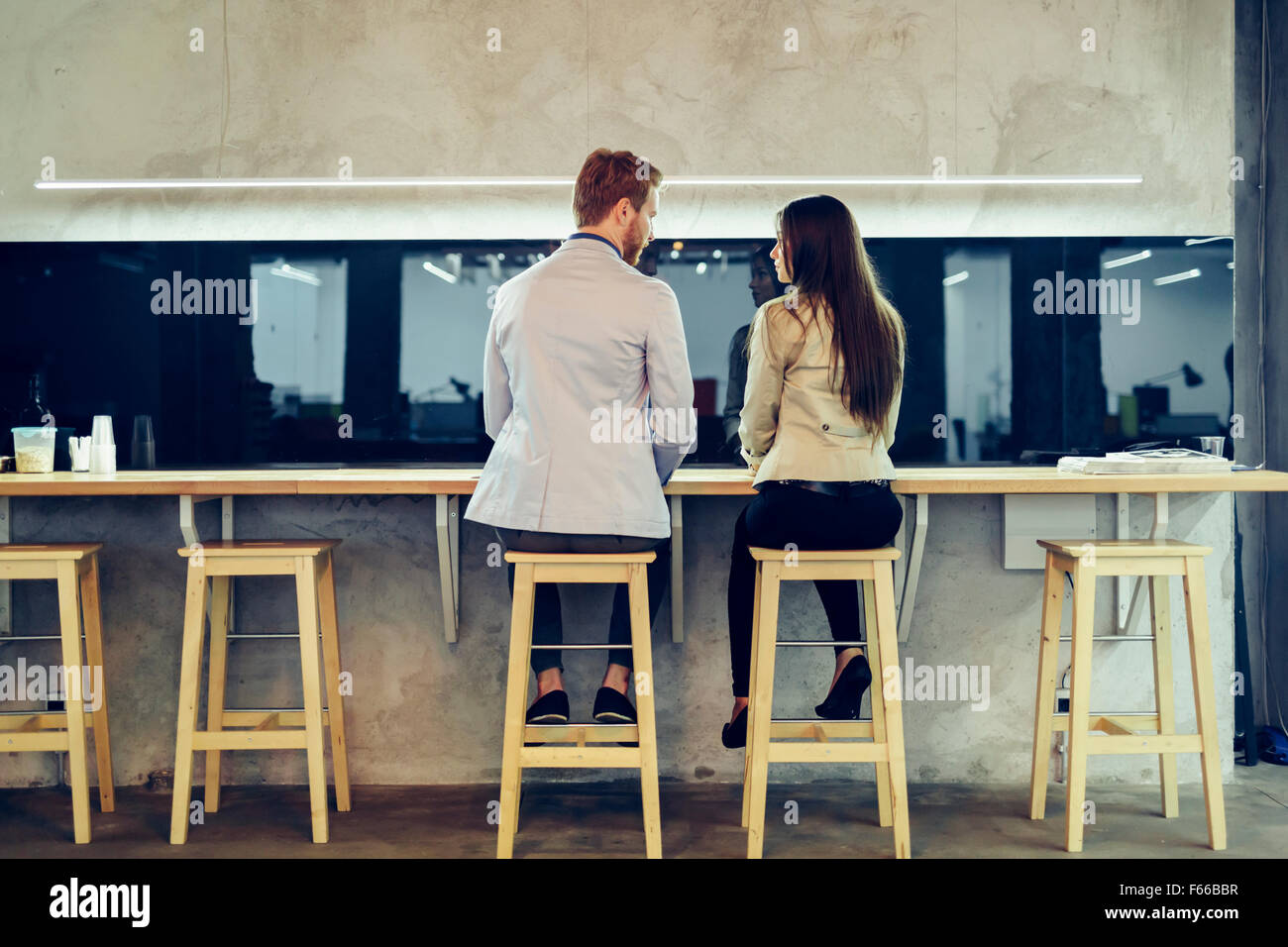 Young colleagues flirting in a bar and talking while sitting on chairs - Stock Image