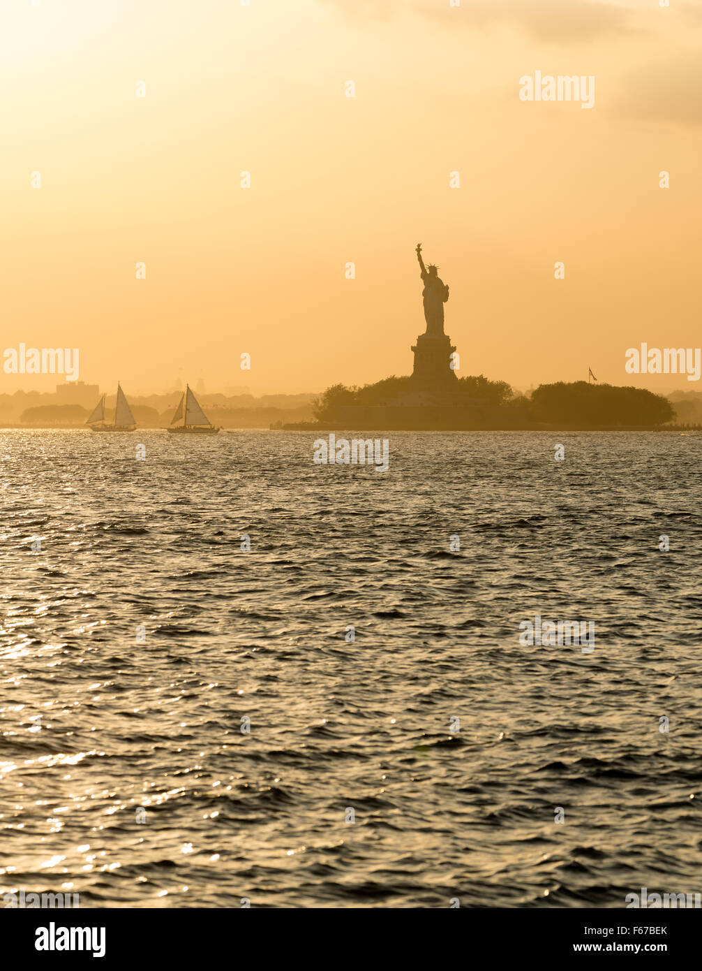 Statue of Liberty before sunset in hazy New York Harbor - Stock Image