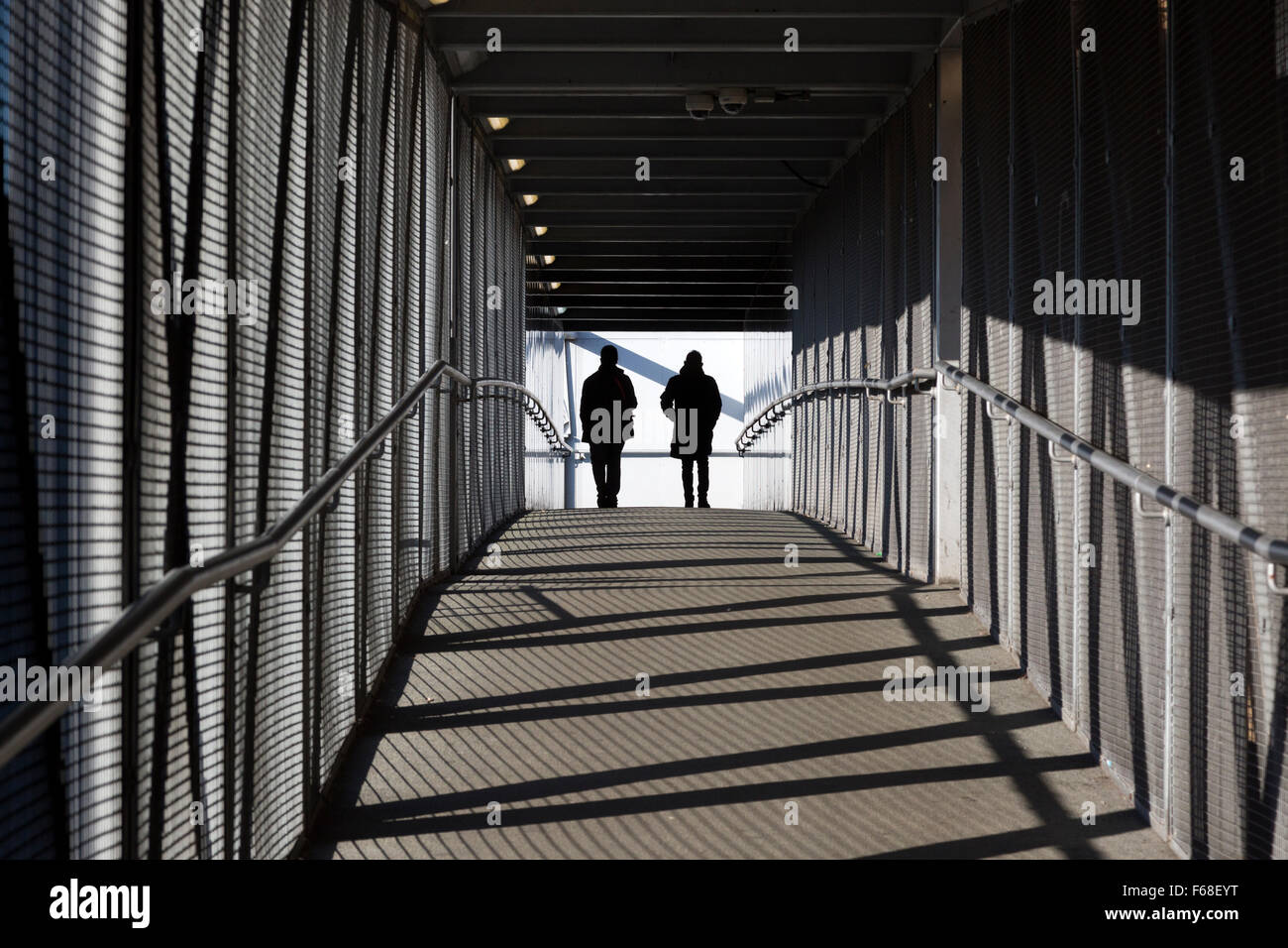 people-crossing-bridge-over-the-railway-feltham-middlesex-F68EYT.jpg