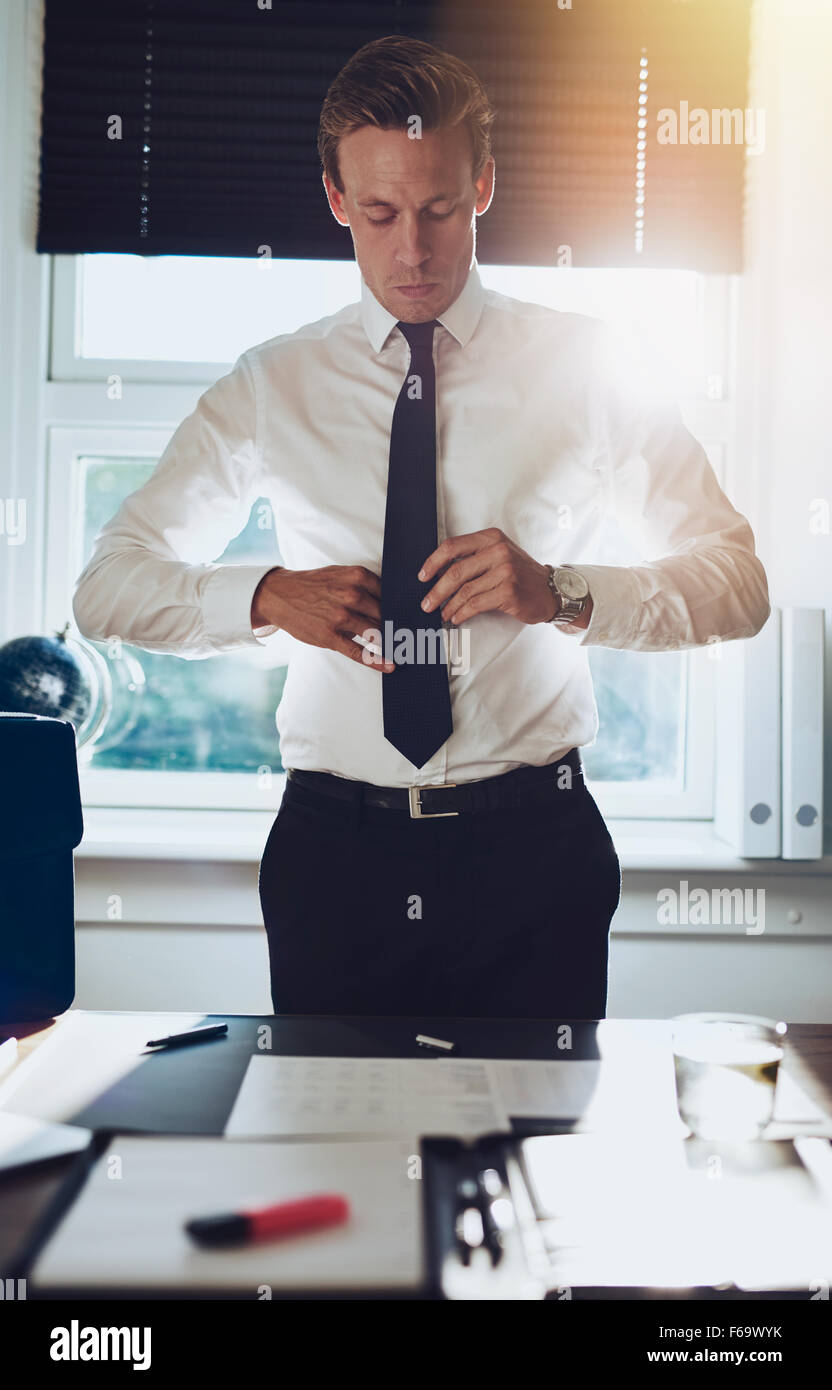 CEO executive business type white male tying his tie while standing at desk at his office, success concept - Stock Image