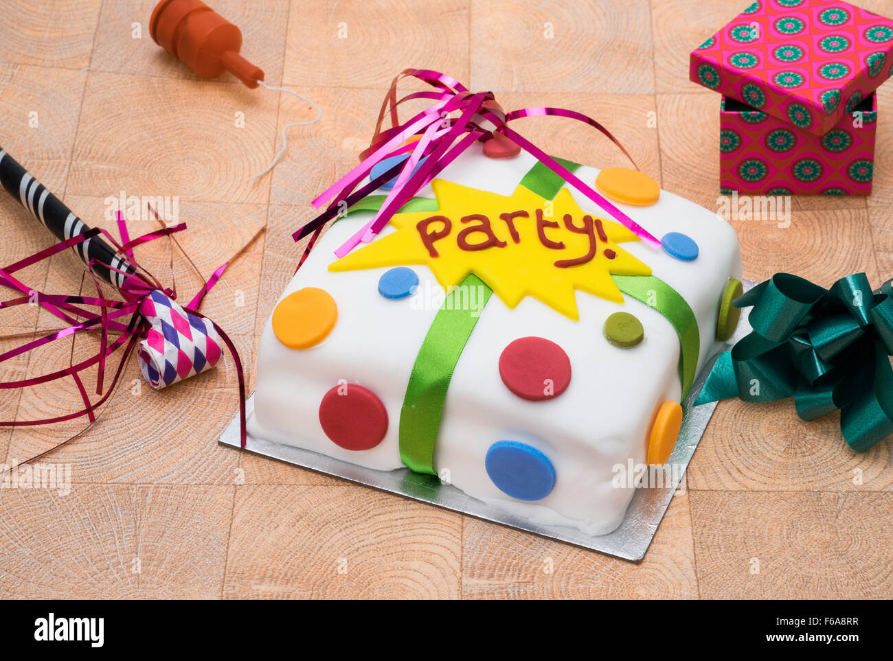 A party celebration cake with various party items - Stock Image