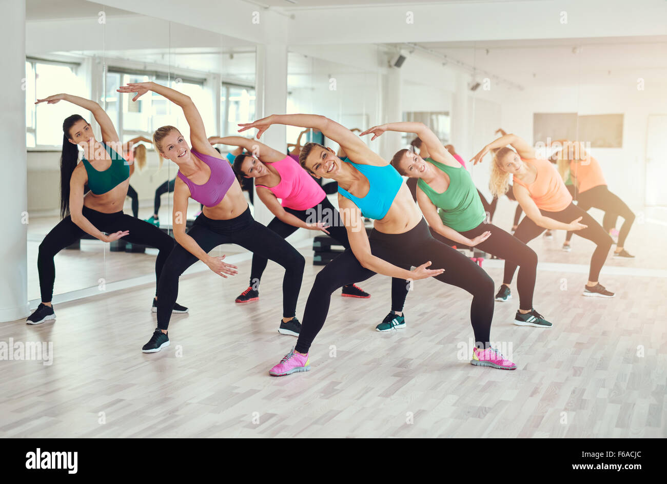 Aerobics class at a gym with a group of attractive fit young women in colorful sportswear working out in synchronisation, - Stock Image