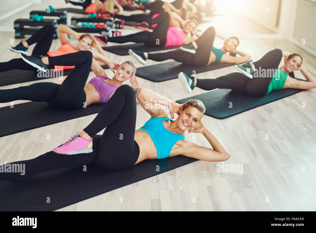 Group of fit healthy young women in a gym wearing colorful sportswear working out in an aerobics class in a healthy - Stock Image