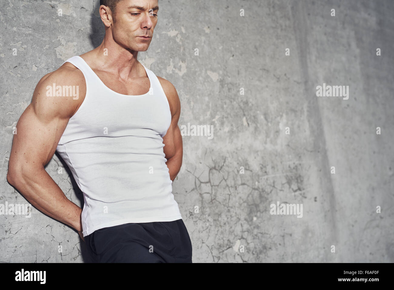 Close up fitness concept portrait of white man, fit and healthy, white tanktop, fitness concept - Stock Image