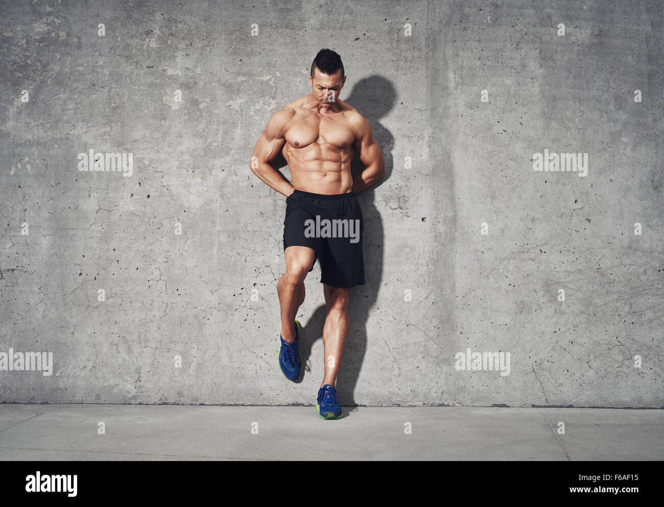 Fitness model standing against grey background, no shirt showing abdominal muscles, room for copy space, fitness - Stock Image