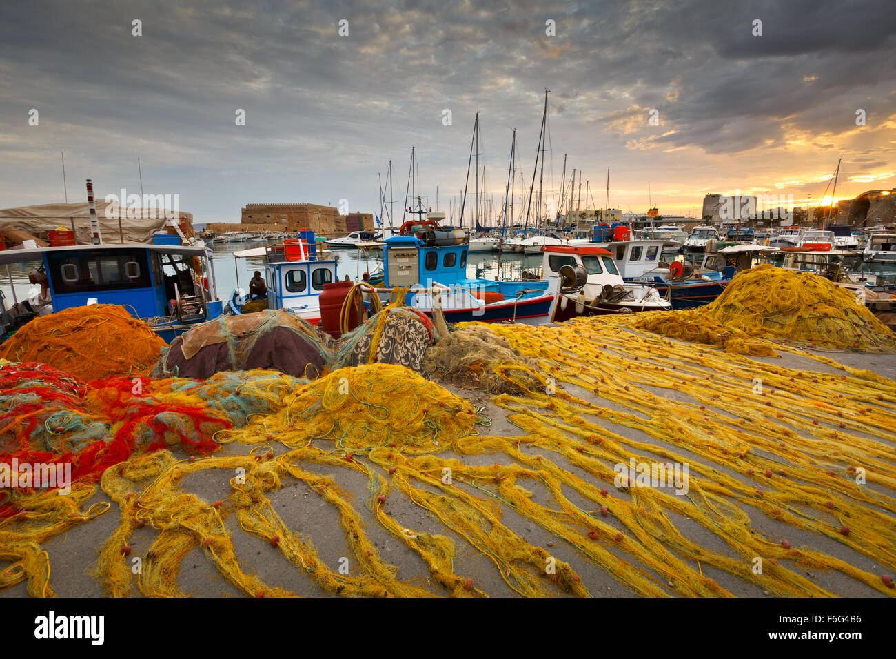 Fishing boats and fishing nets in the old harbour of Heraklion in Crete, Greece - Stock Image