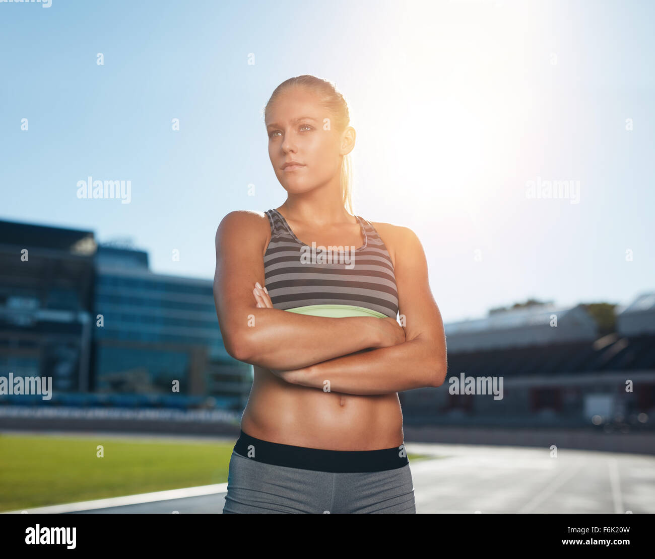 Portrait of fit young woman in sportswear standing on racetrack with her hands folded and looking away. Professional - Stock Image