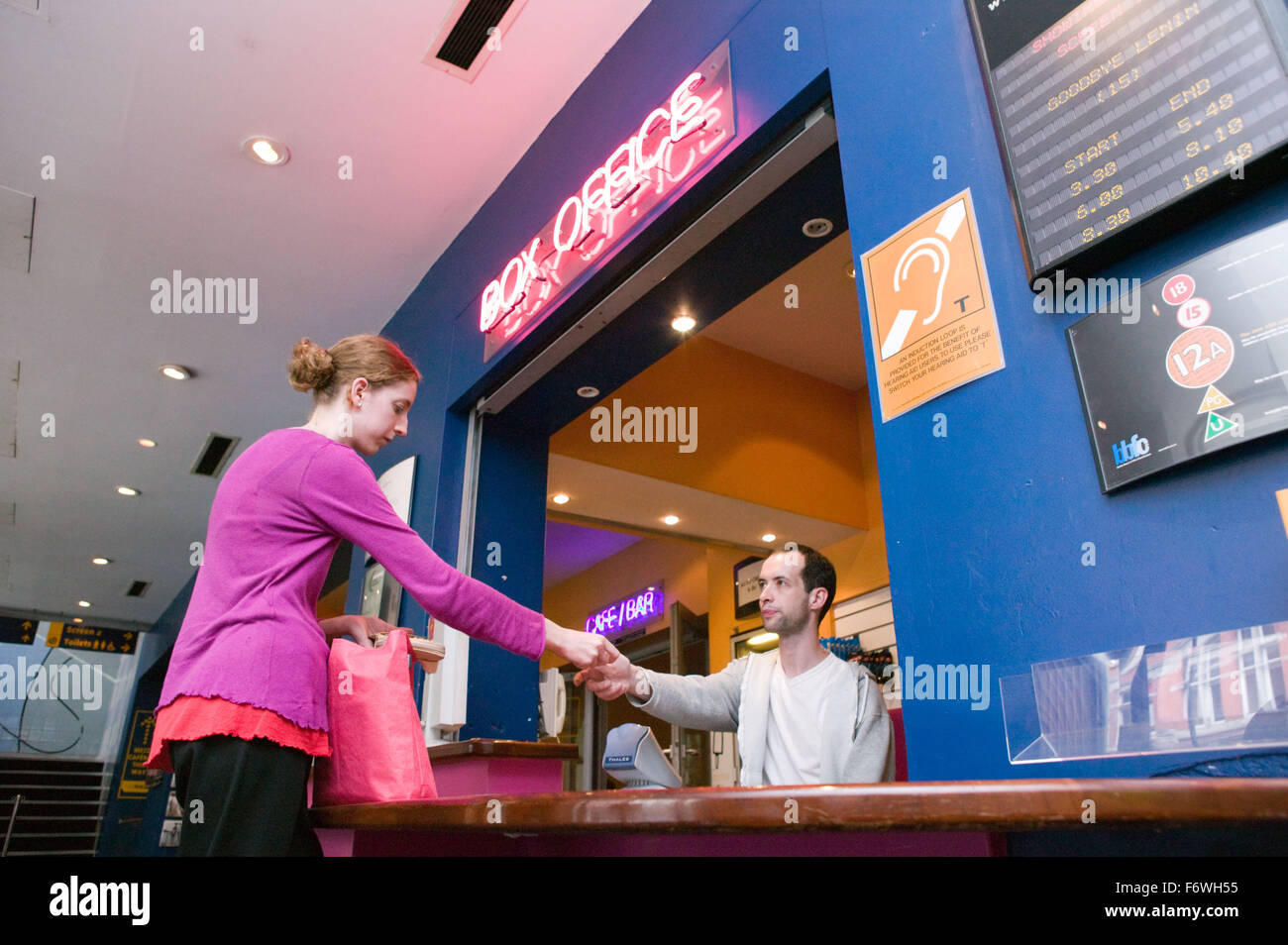 Young woman buying a ticket to see a film at a cinema, A sign shows that an induction loop is available for people - Stock Image