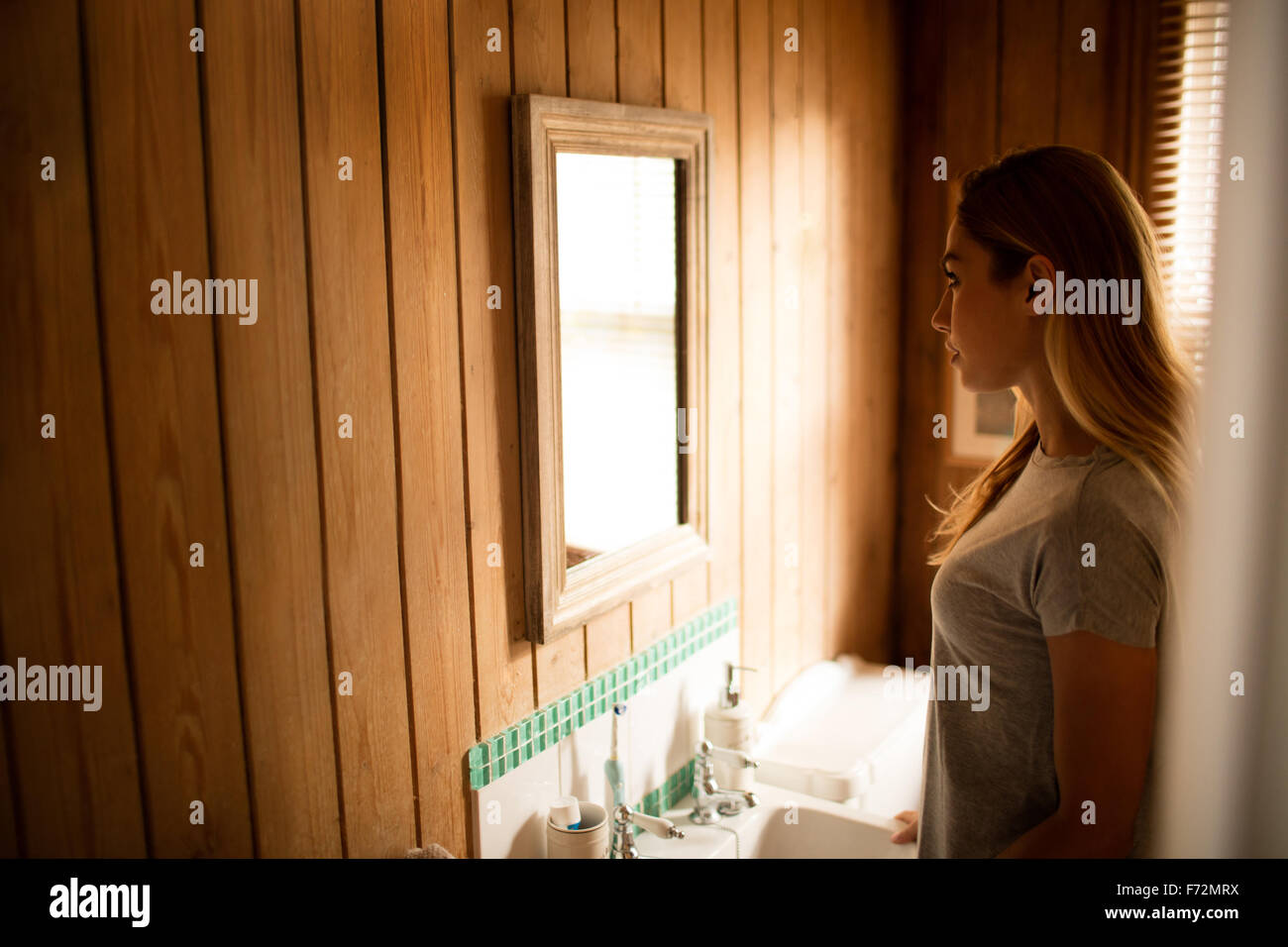 Pretty woman looking at herself in the mirror - Stock Image