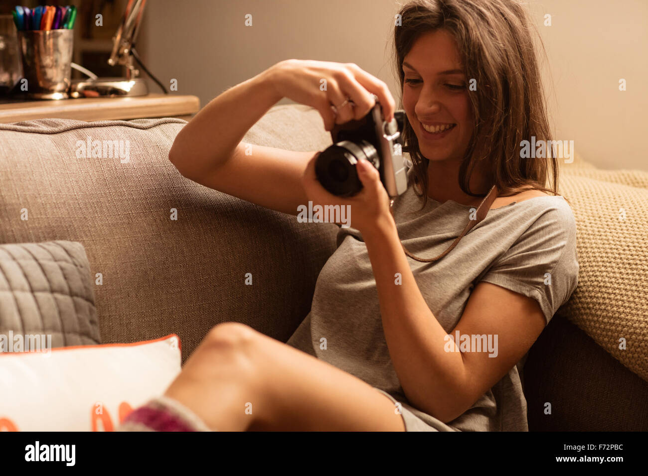 Smiling woman taking pictures with camera - Stock Image