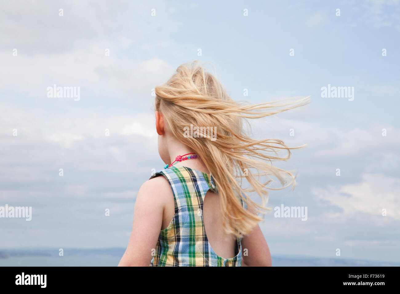 A girl with her hair blowing in the wind. - Stock Image