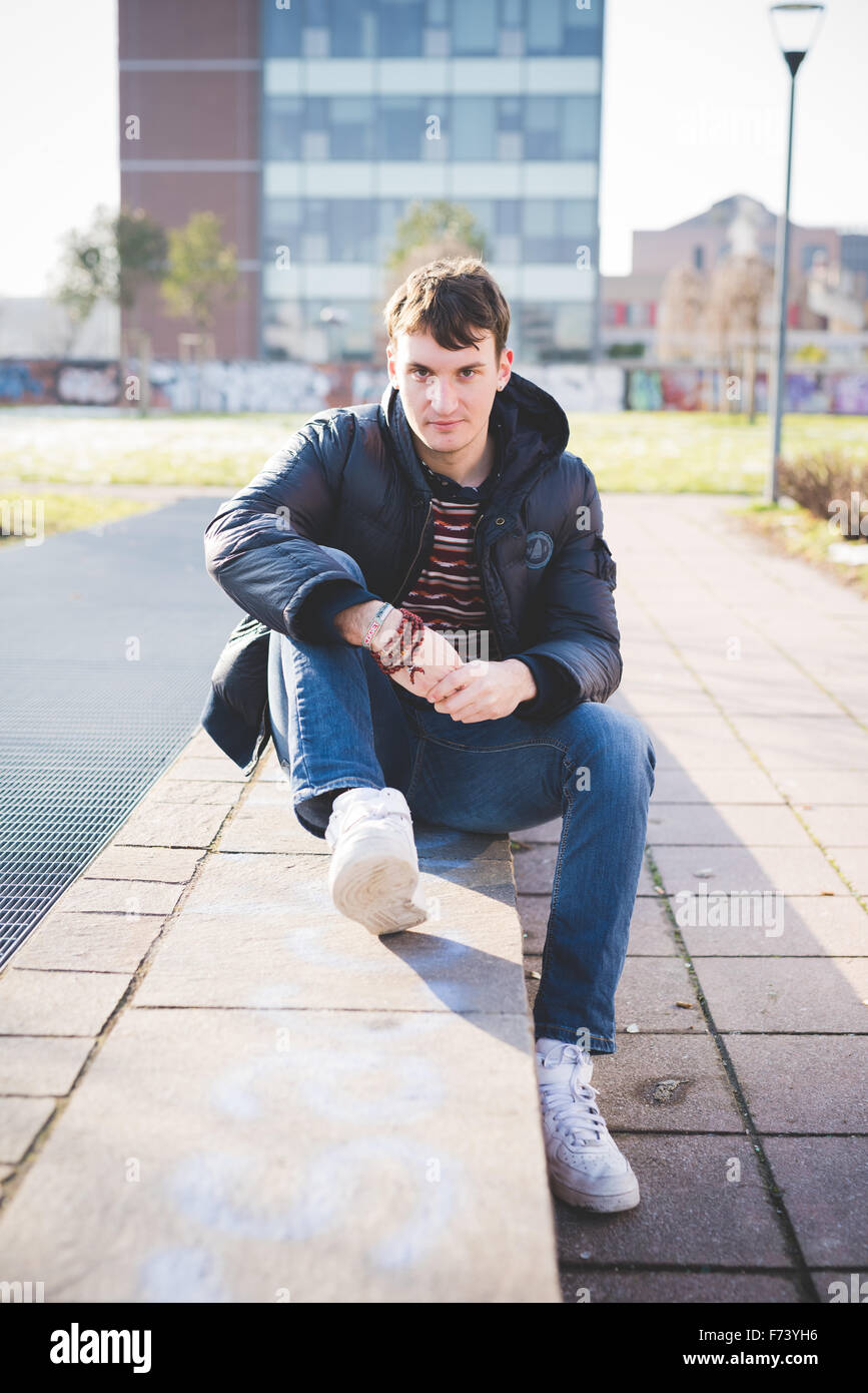 young handsome caucasian brown hair man sitting on a small wall, looking in camera, smiling - youth, carefree concept - Stock Image