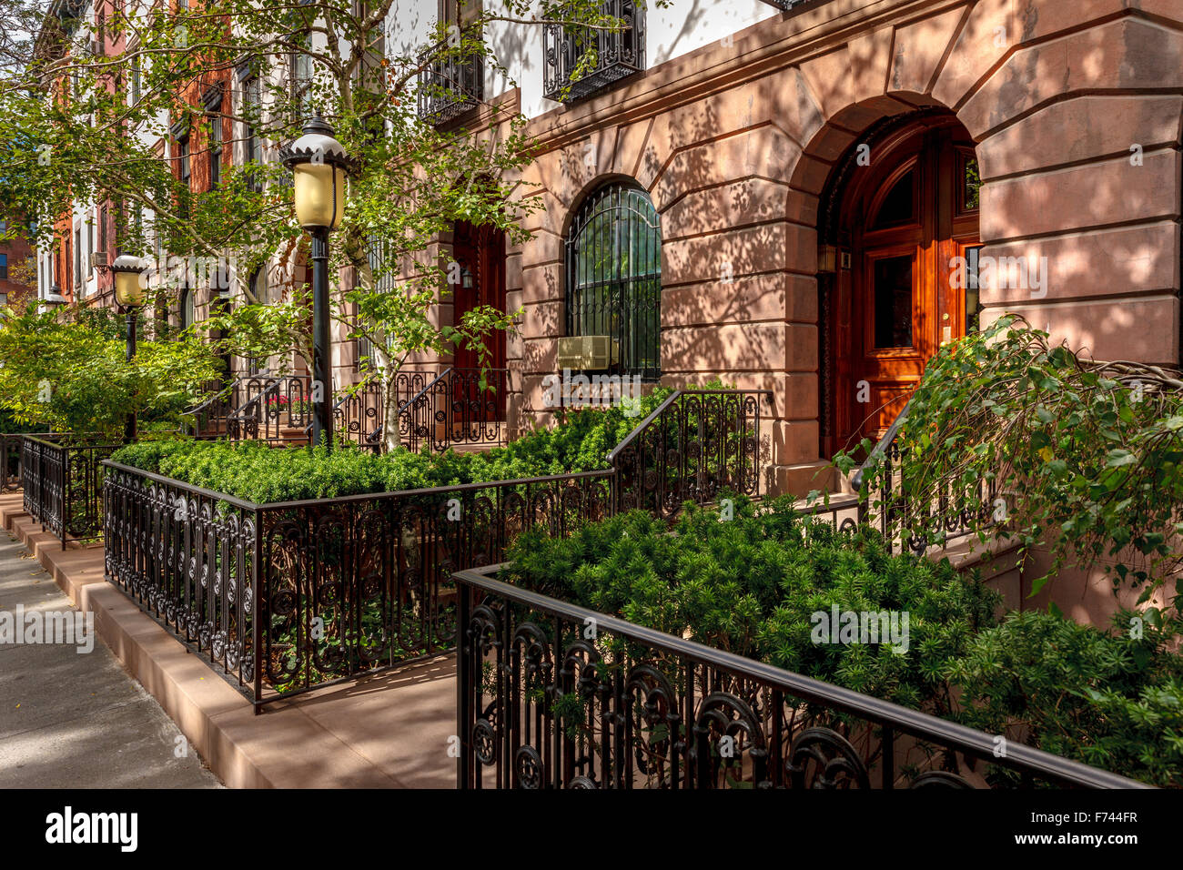 Row of townhouses and their lovely front yards and lampposts. Afternoon light in Chelsea, Manhattan, New York City. - Stock Image