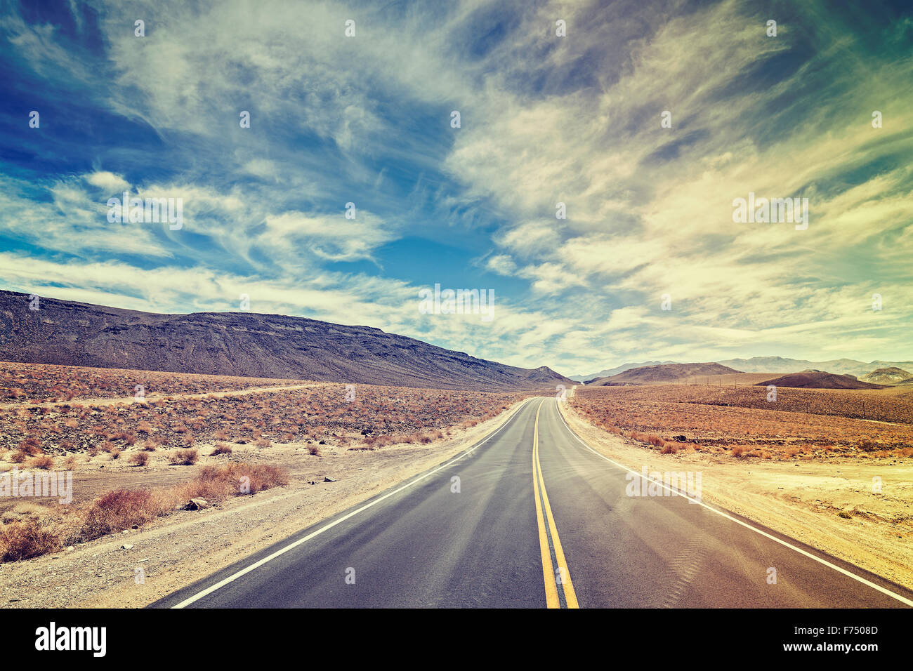 Vintage stylized endless country highway in Death Valley, California, USA. - Stock Image