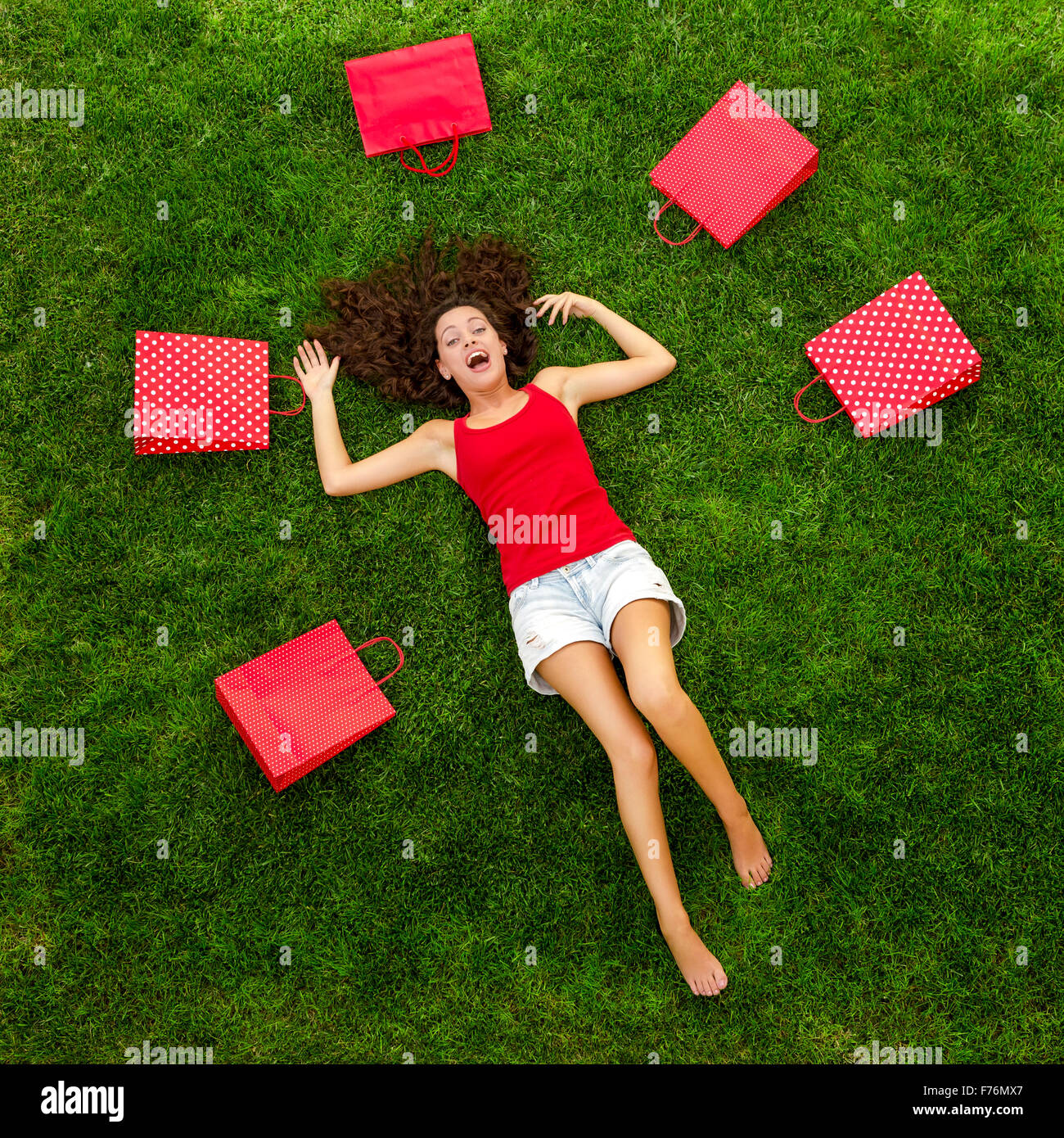 Beautiful and happy young woman lying on the grass surrounded by red gift bags - Stock Image