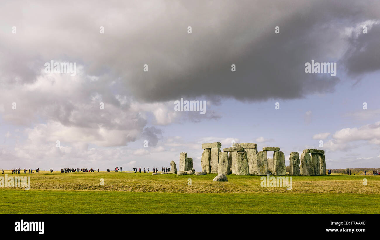 Stonehenge, prehistoric monument, set against the groups of visitors and a blue sunny sky. Stock Photo