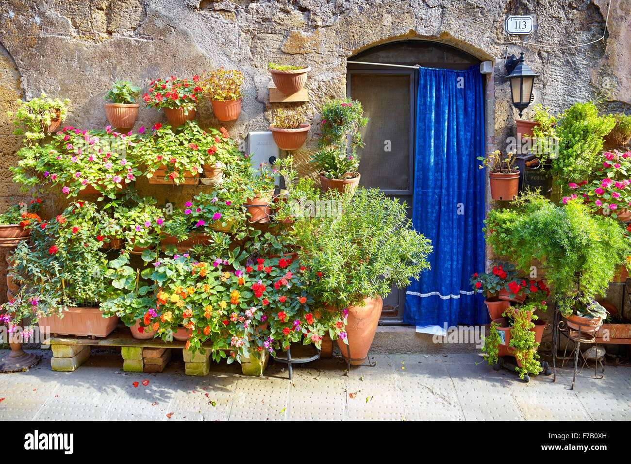 City street decorated with flowers, Pitigliano, Tuscany, Italy - Stock Image