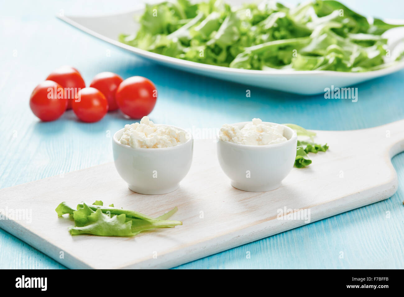 Cottage cheese in two white bowls on blue wooden table, salad and tomato - Stock Image