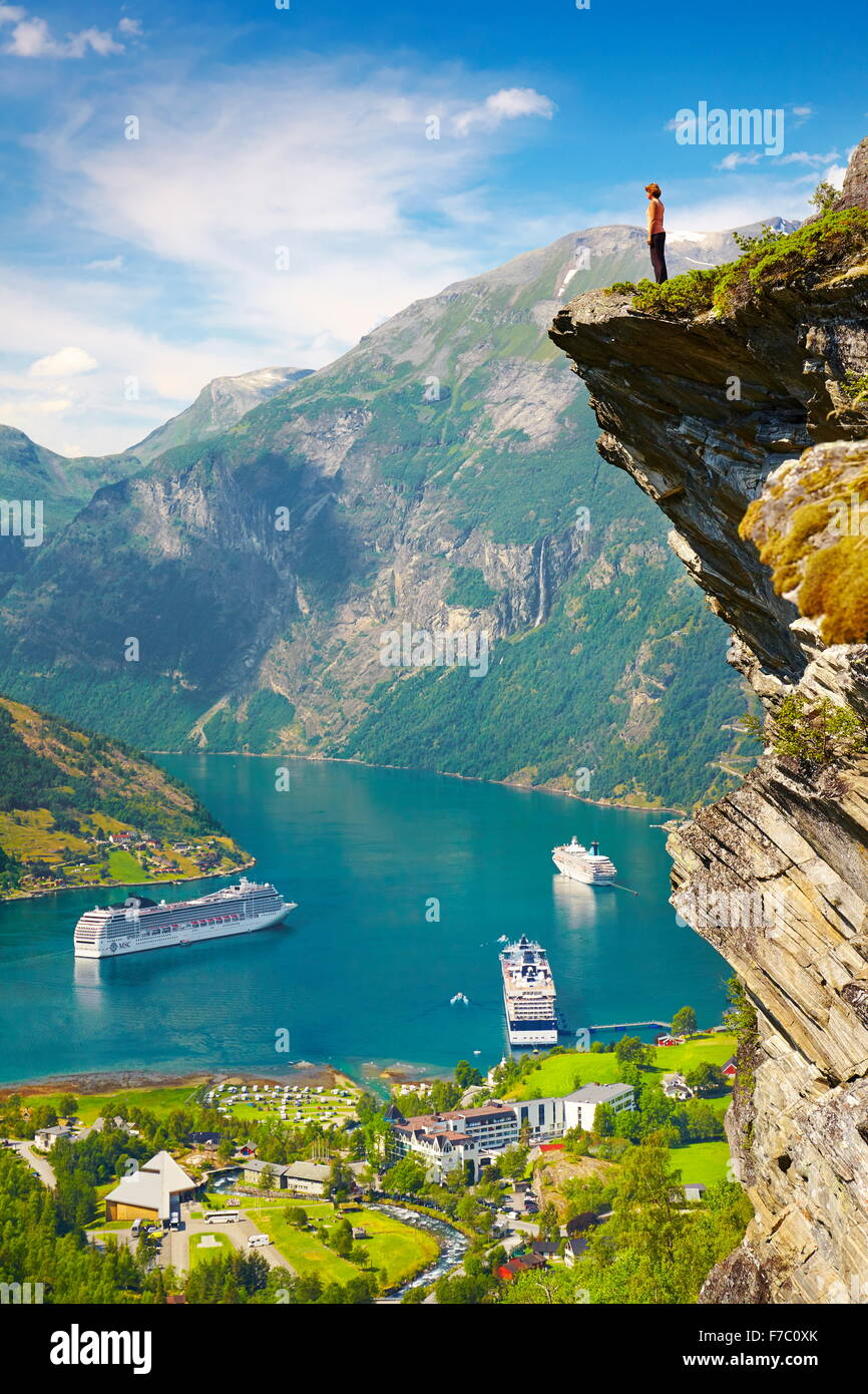 Tourist standing on the rock cliff, cruise ships in the background, Geiranger Fjord, Norway - Stock Image