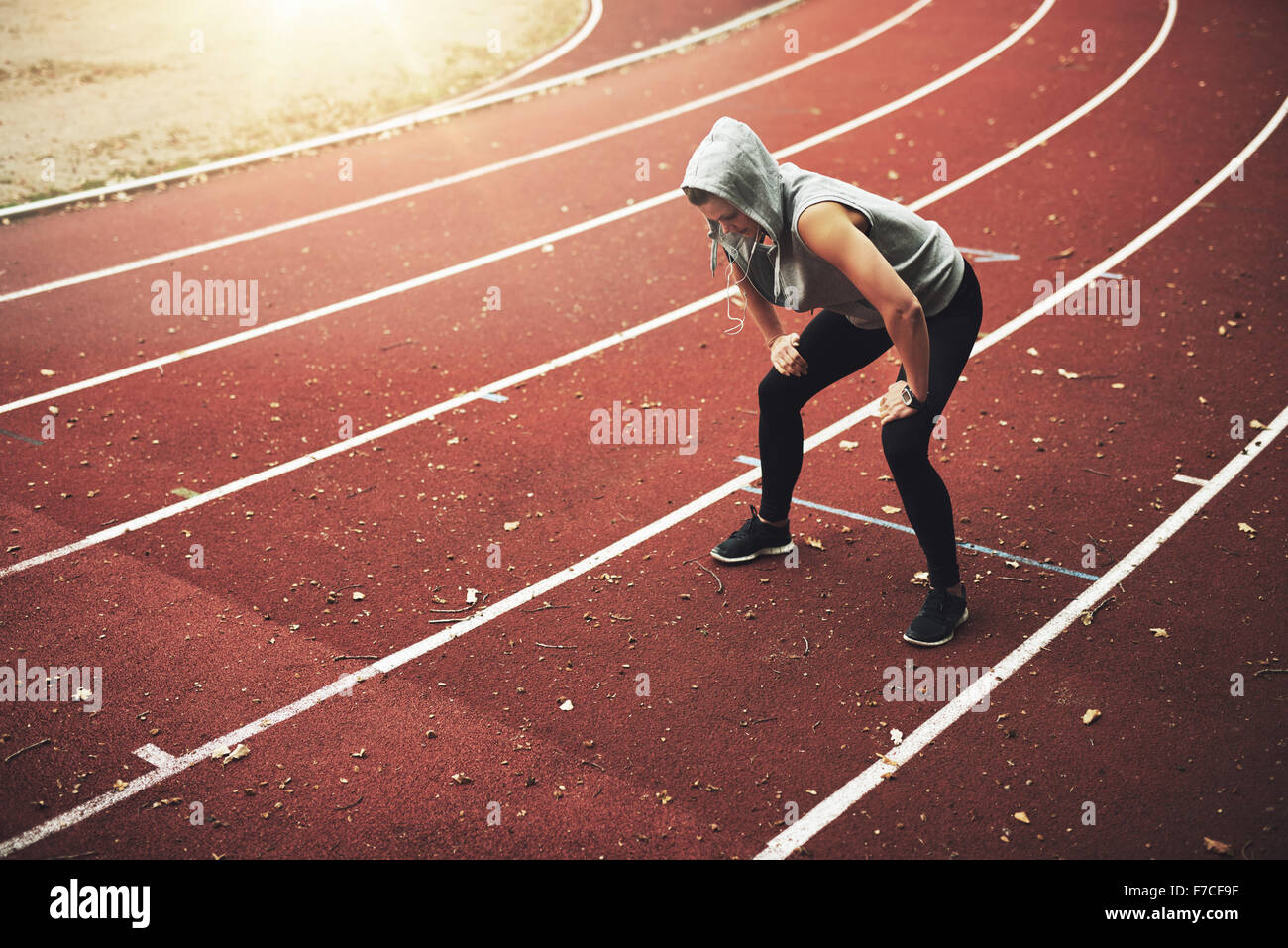 Young female runner standing on stadium and listening to music, relaxing after running - Stock Image