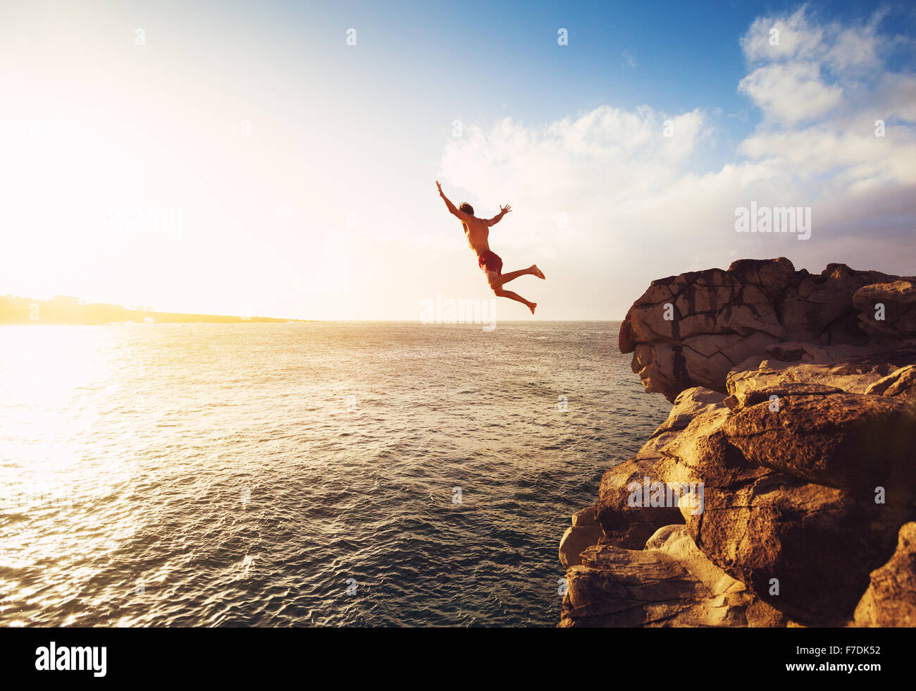Cliff Jumping into the Ocean at Sunset, Summer Fun Lifestyle - Stock Image