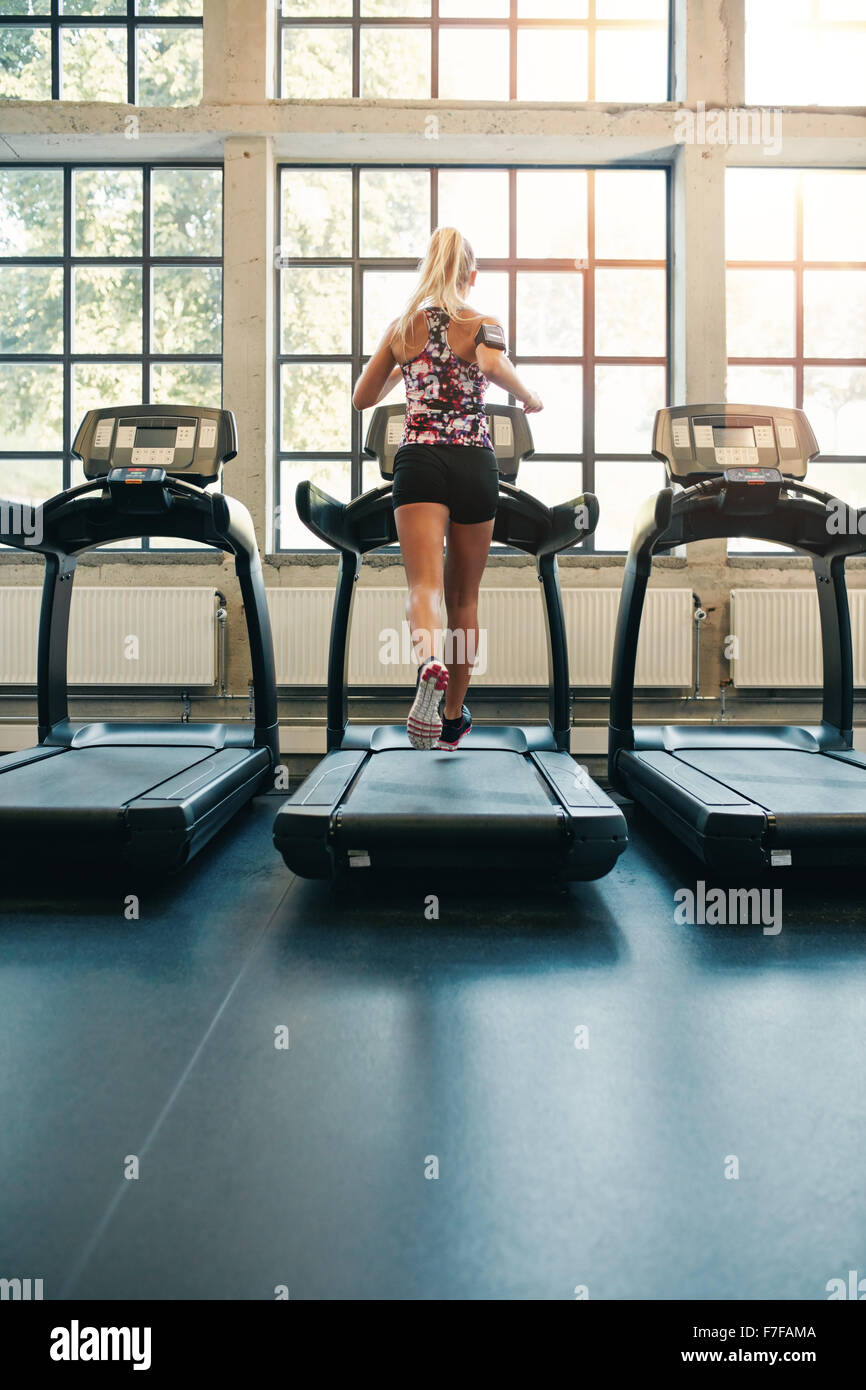 Rear view of young female running on treadmill in gym. Fitness woman jogging indoors in health club - Stock Image
