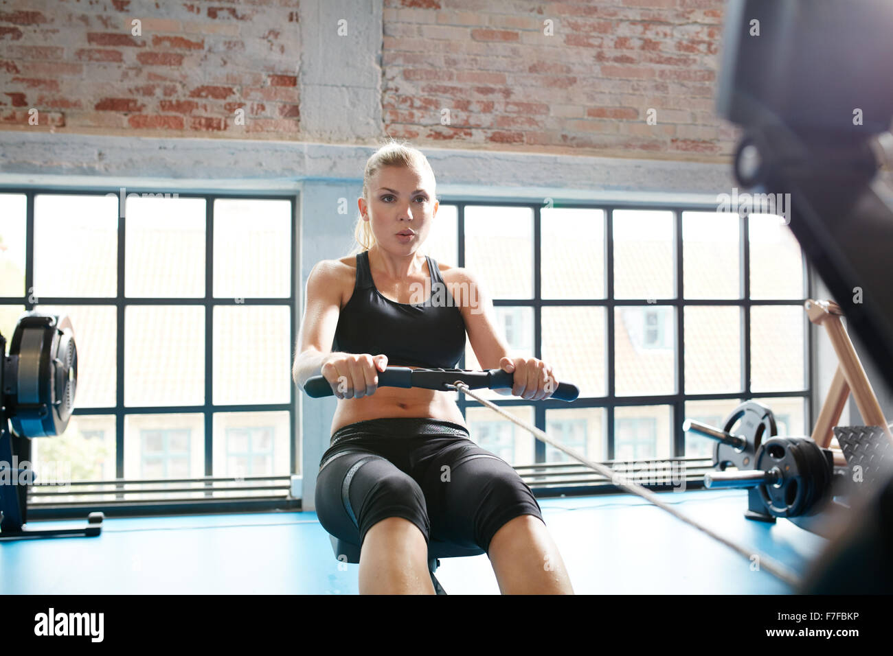 Caucasian female using rowing machine in the gym. Young woman doing cardio workout in fitness club. - Stock Image