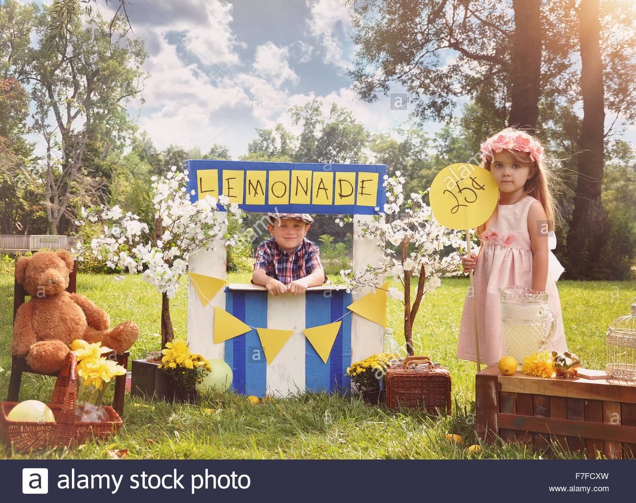 Two little kids are selling lemonade at a homemade lemonade stand on a sunny day with a price sign for an entrepreneur - Stock Image