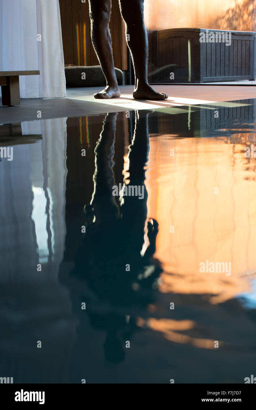 Man's reflection on spa swimming pool, low section - Stock Image