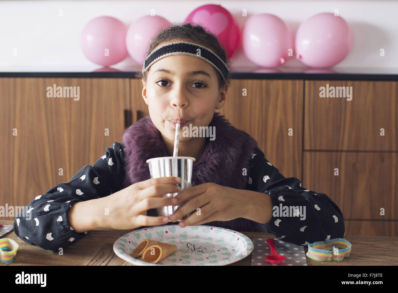 Girl drinking through a straw - Stock Image