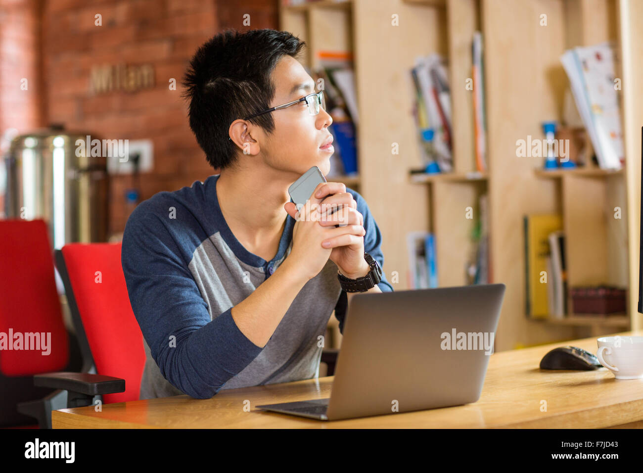 Thoughtful young asian man in glasses using laptop in cafe - Stock Image