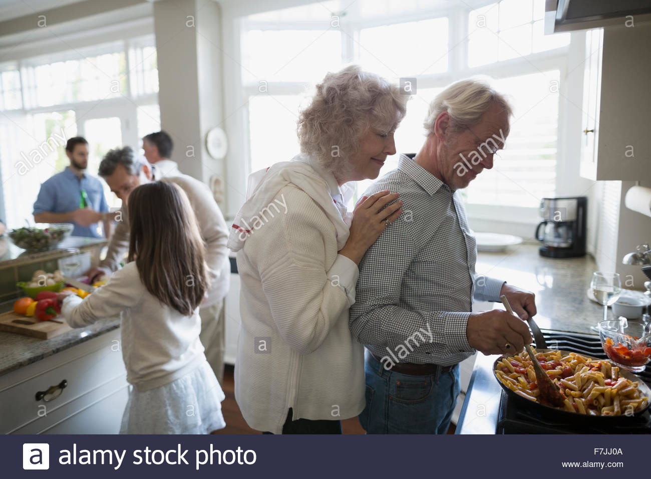 Senior couple cooking at kitchen stove - Stock Image