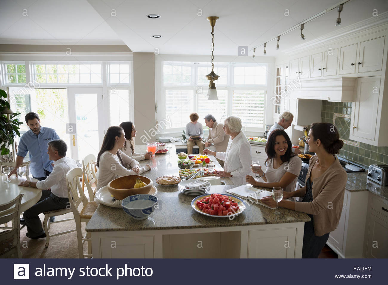 Multi-generation family gathering and cooking in kitchen - Stock Image